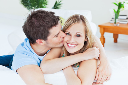 Portrait of an attentive boyfriend kissing his smiling girlfriend relaxing in the living-room