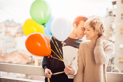 Young couple in love at balcony holding balloons